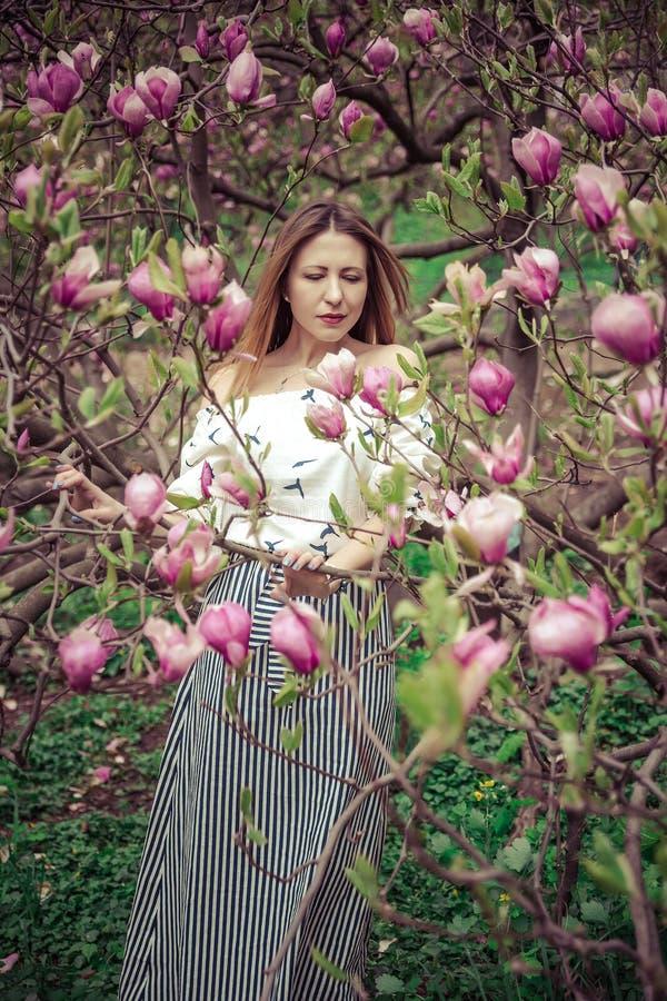 Mujer caucásica hermosa joven en el jardín floreciente de la primavera de magnolias La muchacha en el jardín en un día nublado imágenes de archivo libres de regalías