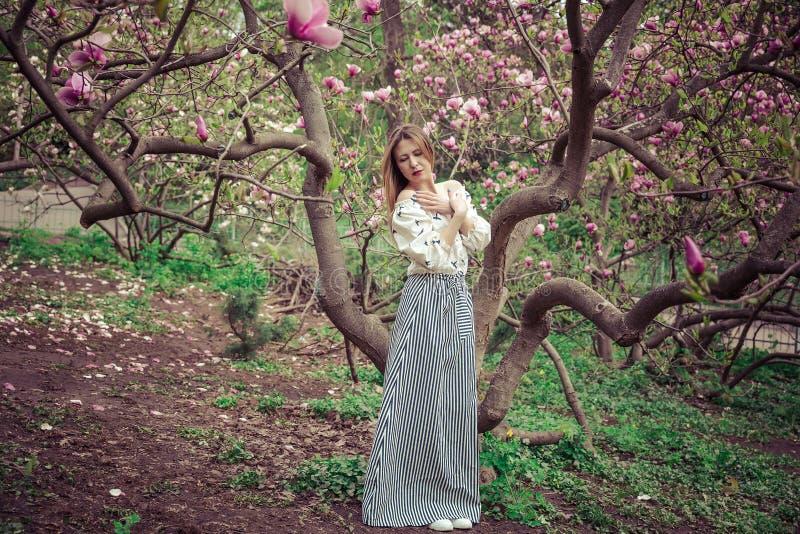 Mujer caucásica hermosa joven en el jardín floreciente de la primavera de magnolias La muchacha en el jardín en un día nublado foto de archivo