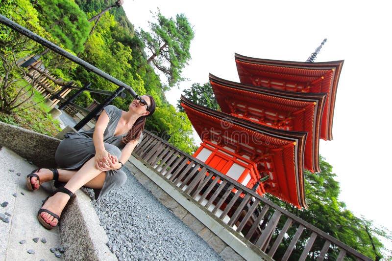 Mujer caucásica hermosa joven que presenta delante de la cámara con la pagoda de Koyasu en el fondo, templo de Kiyomizu-dera, Kyo foto de archivo