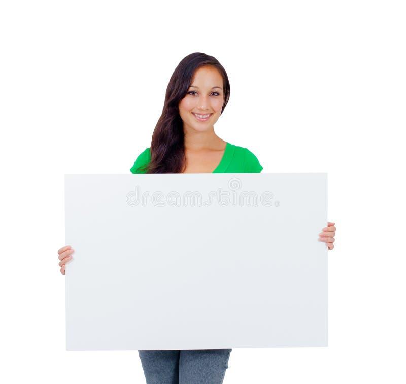 Mujer caucásica hermosa que lleva a cabo una muestra en blanco fotografía de archivo libre de regalías