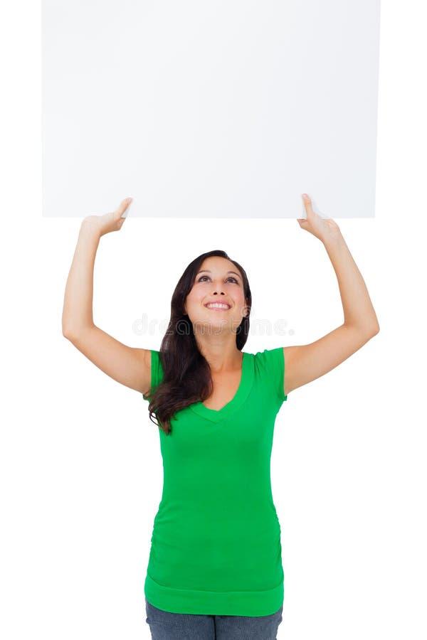 Mujer caucásica hermosa que lleva a cabo una muestra en blanco imagenes de archivo