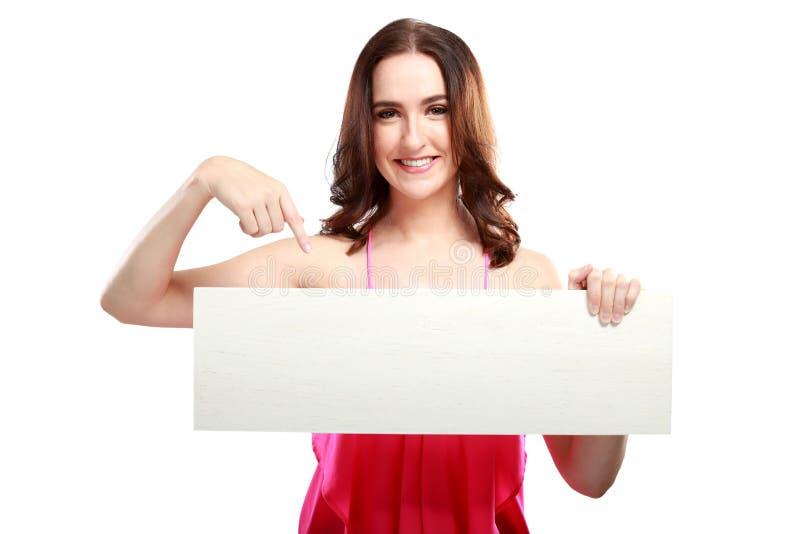 Mujer caucásica hermosa que se sostiene y que señala en el tablero blanco fotos de archivo libres de regalías