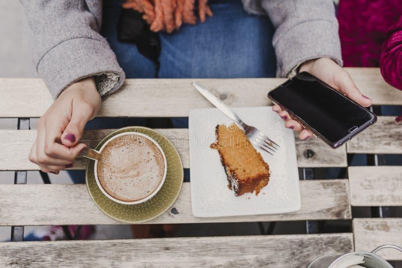 Mujer caucásica irreconocible joven que goza de una taza de café y de un pedazo de torta en una terraza con los amigos Aire libre imagen de archivo