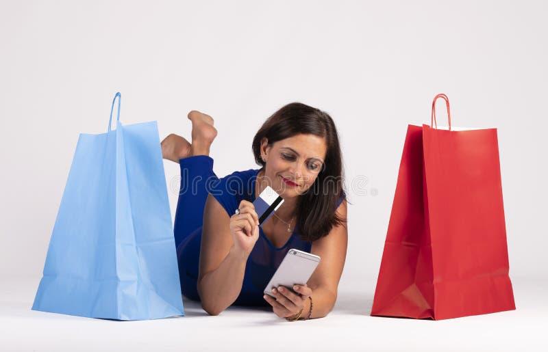 Mujer caucásica joven bonita que miente en el piso que mira el teléfono móvil y que usa la tarjeta de crédito junto con algunos e imagenes de archivo