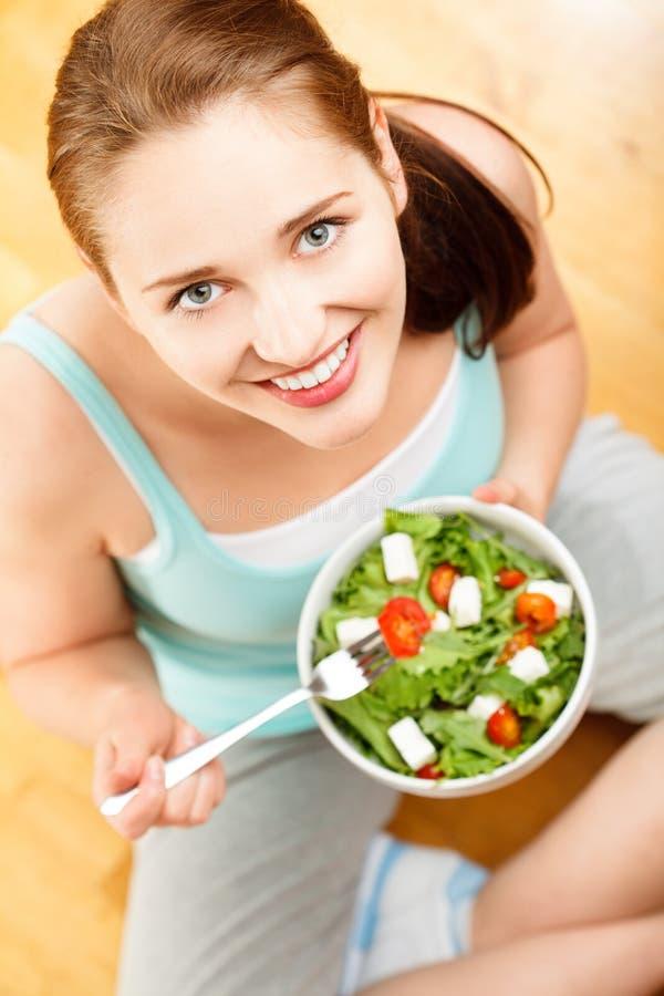 Mujer caucásica joven del alto retrato dominante que come la ensalada en casa imagenes de archivo