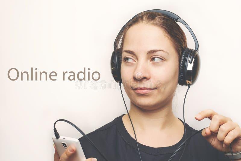 Mujer caucásica joven en auriculares en la radio en línea principal de la música que escucha o podcast del smartphone móvil, entr foto de archivo