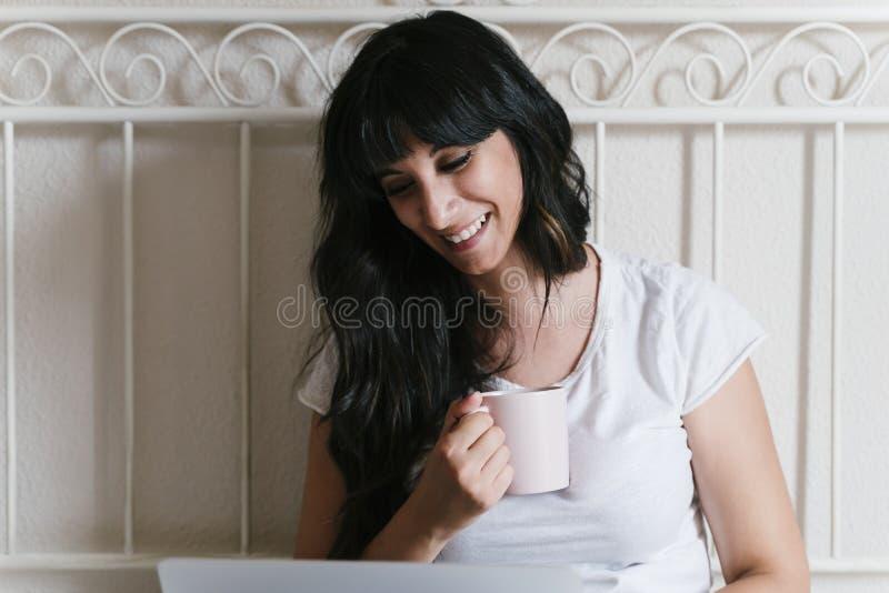 Mujer caucásica joven en casa en la cama que come una taza de café o de té Trabajo en el ordenador port?til Mañana y relajar conc foto de archivo libre de regalías