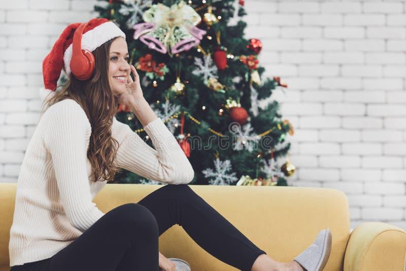 Mujer caucásica joven en el sombrero rojo que se sienta en el sofá que escucha MU foto de archivo
