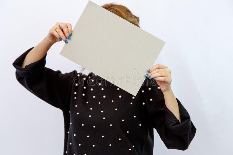 Mujer caucásica joven en un fondo aislado blanco que sostiene una hoja de la cartulina sin etiquetas foto de archivo