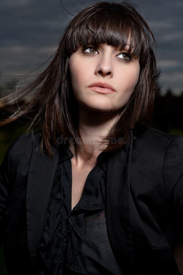 Mujer caucásica joven en un parque con el cielo tempestuoso fotos de archivo