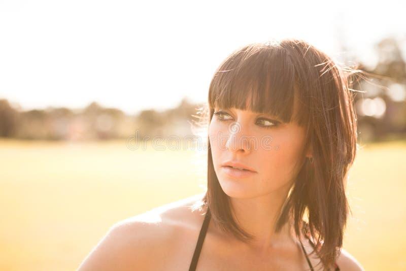 Mujer caucásica joven en un parque con la luz suave imagenes de archivo