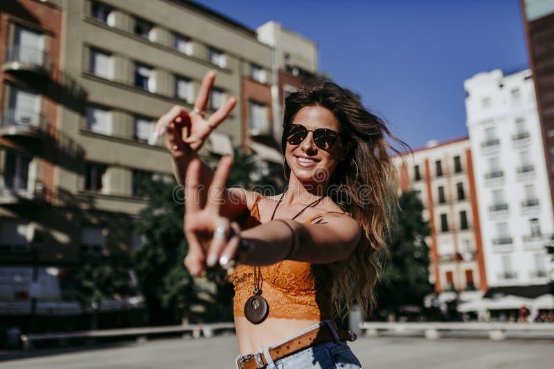 Mujer caucásica joven hermosa en la calle de la ciudad en un día soleado que hace el gesto V con los fingeres con la sonrisa feli fotos de archivo libres de regalías