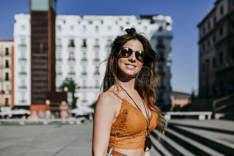 Mujer caucásica joven hermosa que camina en la calle de la ciudad en un día soleado Sonrisa feliz de la cara Forma de vida urbana fotos de archivo libres de regalías