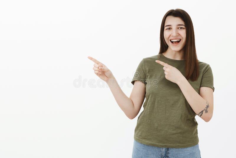 Mujer caucásica joven optimista alegre y enérgica con el tatuaje en el brazo que ríe hacia fuera ruidosamente divirtiéndose y señ imagen de archivo