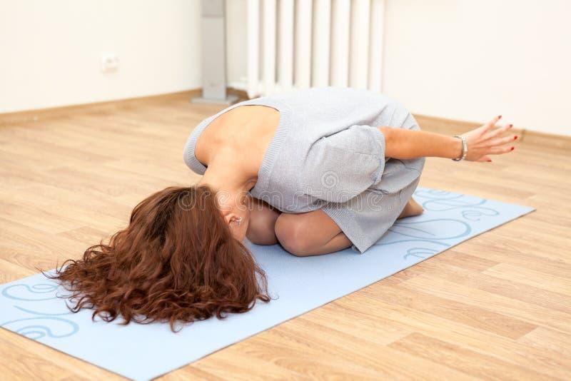 Mujer caucásica joven que hace ejercicios aeróbicos en la estera imagen de archivo libre de regalías