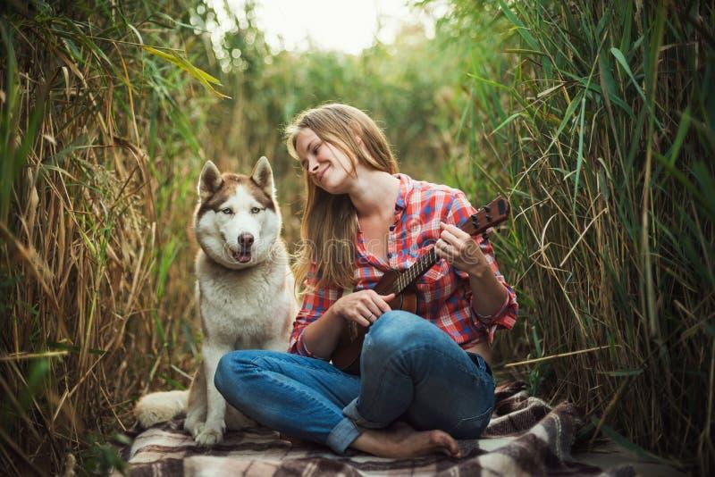 Mujer caucásica joven que juega el ukelele con el perro esquimal fotos de archivo