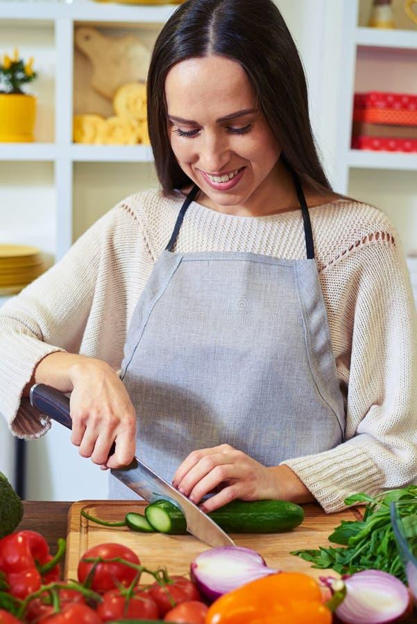 Mujer caucásica joven que se coloca en la cocina y que corta el cucumb foto de archivo