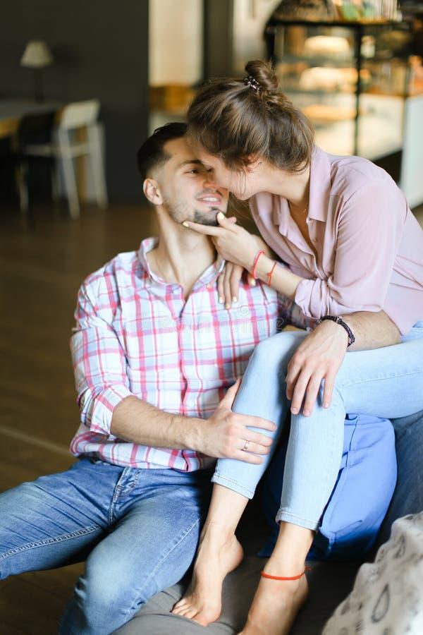 Mujer caucásica joven que se sienta con el hombre y besarse fotos de archivo