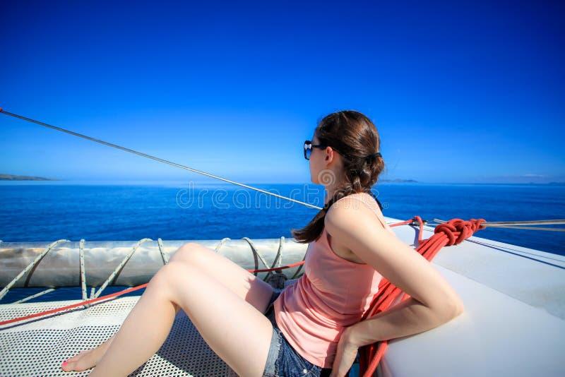 Mujer caucásica joven que se sienta delante de un barco imagen de archivo