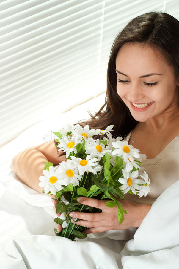 Mujer caucásica joven que se sienta en cama con las flores foto de archivo