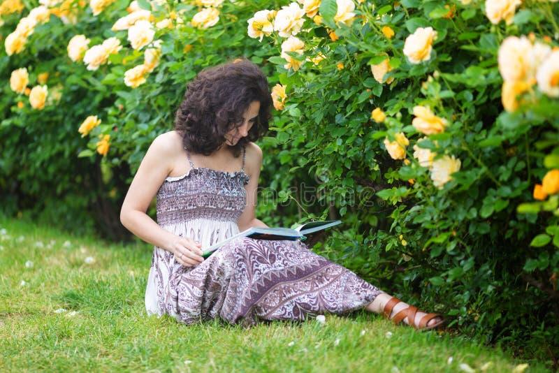 Mujer caucásica joven que se sienta en hierba verde cerca de arbusto de rosas amarillas en una rosaleda, leyendo un libro, mirand fotos de archivo