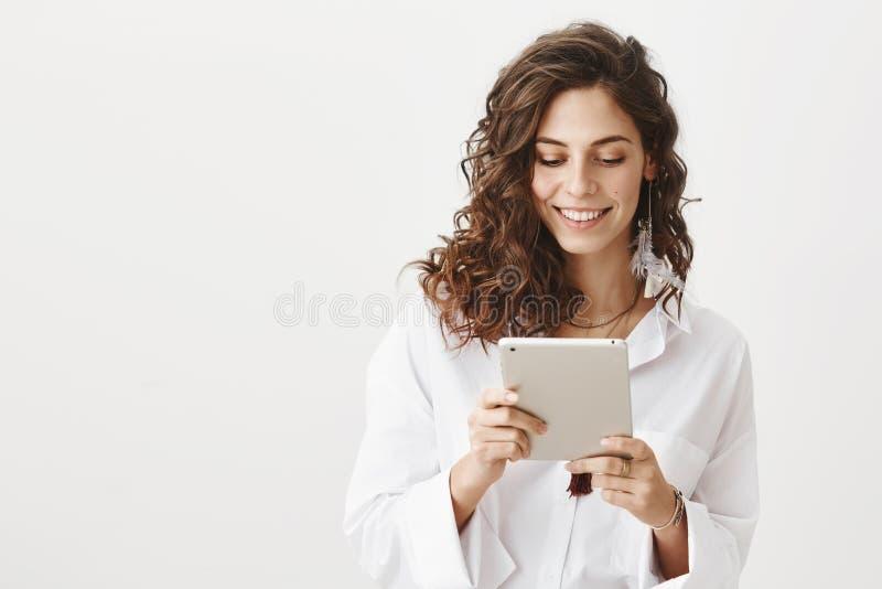 Mujer caucásica linda encantadora en la blusa de moda blanca que hojea en red vía la tableta, sonriendo y expresando felicidad imagen de archivo
