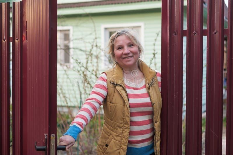 Mujer caucásica madura que abre la cerca roja para acoger con satisfacción a algunas huéspedes foto de archivo libre de regalías