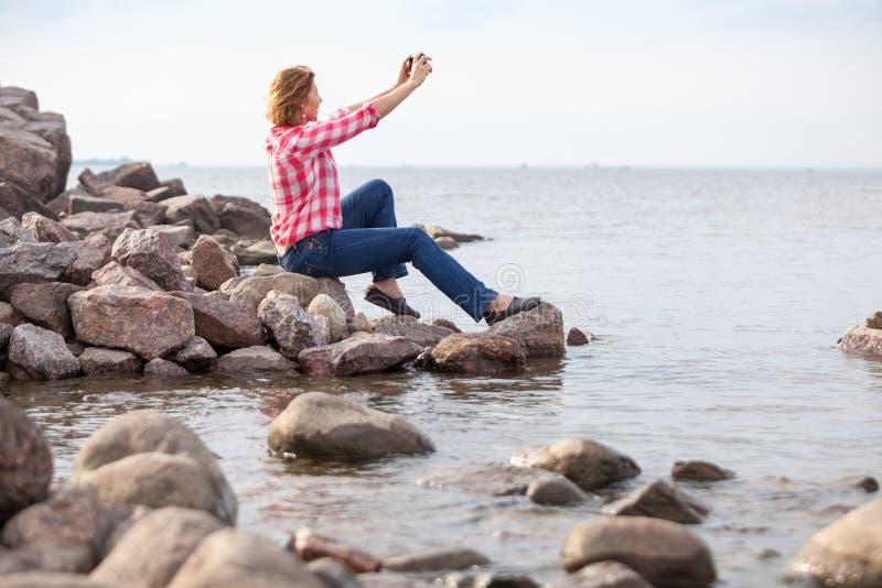 Mujer caucásica madura usando un smartphone para tomarse una selfie mientras se sienta en la orilla rocosa, con camisetas rojas y imágenes de archivo libres de regalías