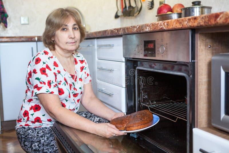 Mujer caucásica mayor con una empanada en las manos que se sientan al lado del horno incorporado en la cocina fotos de archivo
