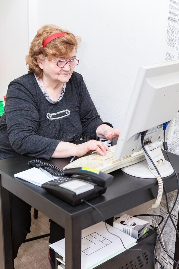Mujer caucásica mayor que trabaja en sitio de la oficina fotografía de archivo libre de regalías
