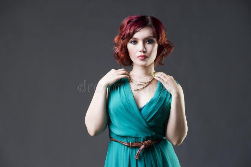 Mujer caucásica pelirroja hermosa joven en el vestido de la aguamarina que presenta en estudio en fondo gris, maquillaje profesio imagen de archivo