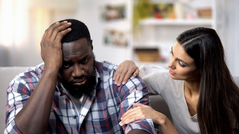 Mujer caucásica que apoya al novio afroamericano, problemas de la vida, tensión fotografía de archivo libre de regalías