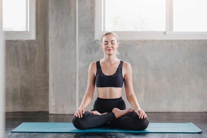 Mujer caucásica que hace meditar de la actitud de la yoga imagenes de archivo