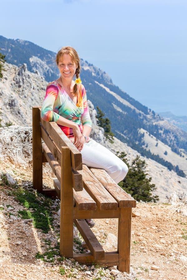 Mujer caucásica que se sienta en banco en paisaje de la montaña fotos de archivo libres de regalías