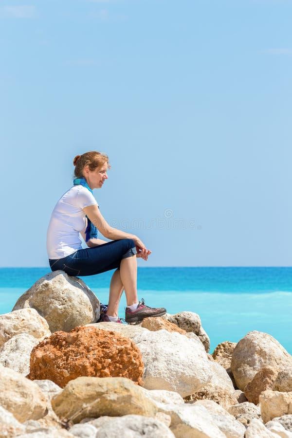 Mujer caucásica que se sienta en rocas en la costa cerca del mar fotografía de archivo