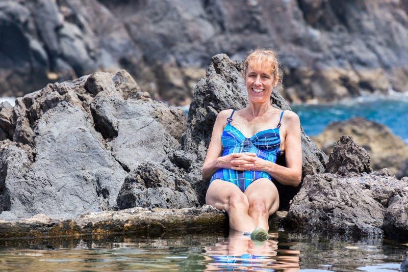 Mujer caucásica que toma el sol en rocas en el agua natural foto de archivo libre de regalías