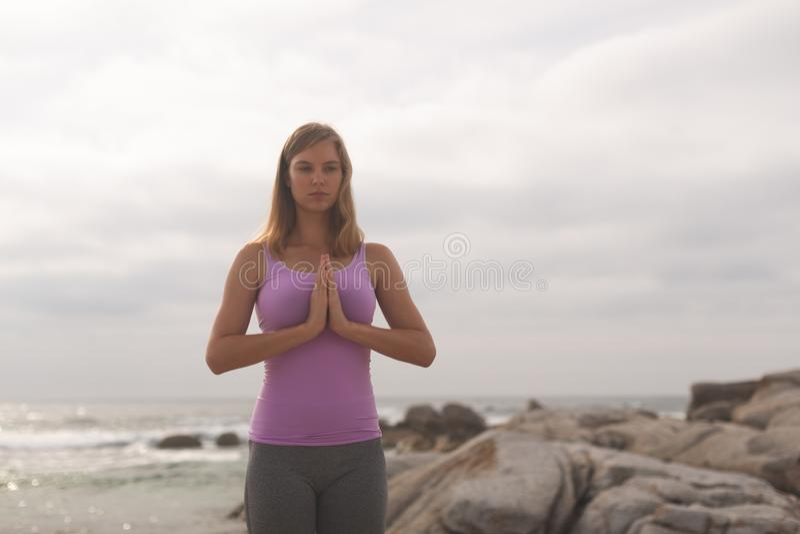 Mujer caucásica realizar yoga en la playa fotos de archivo