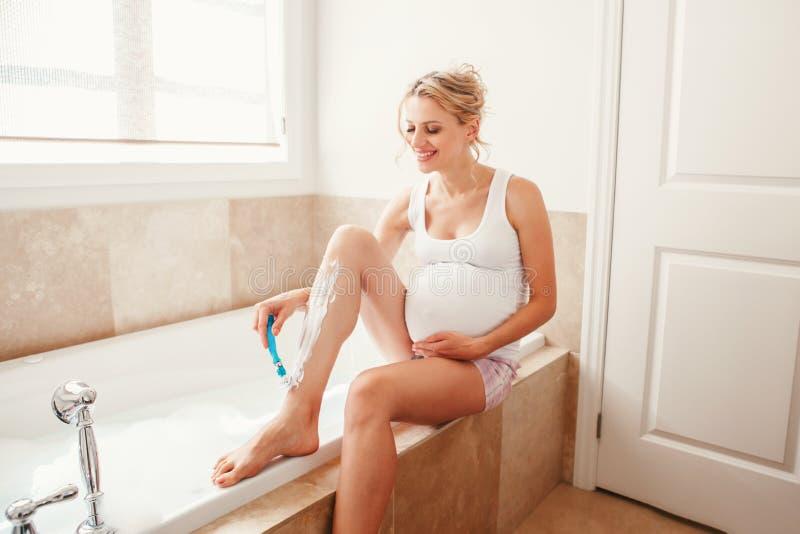 Mujer caucásica rubia embarazada que afeita las piernas en cuarto de baño fotografía de archivo