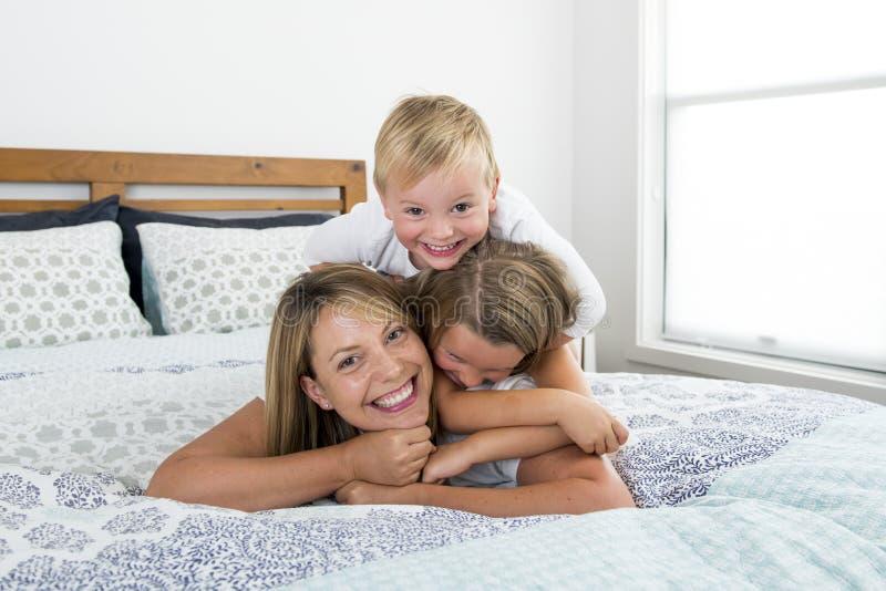 Mujer caucásica rubia joven que miente en cama así como sus pequeños el jugar de risa del hijo del dulce 3 y 7 años y de la hija  foto de archivo