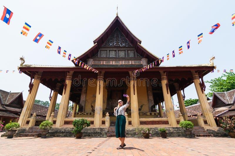 Mujer caucásica rubia que hace el selfie delante de Wat Sisaket en Vientián, Laos imagen de archivo