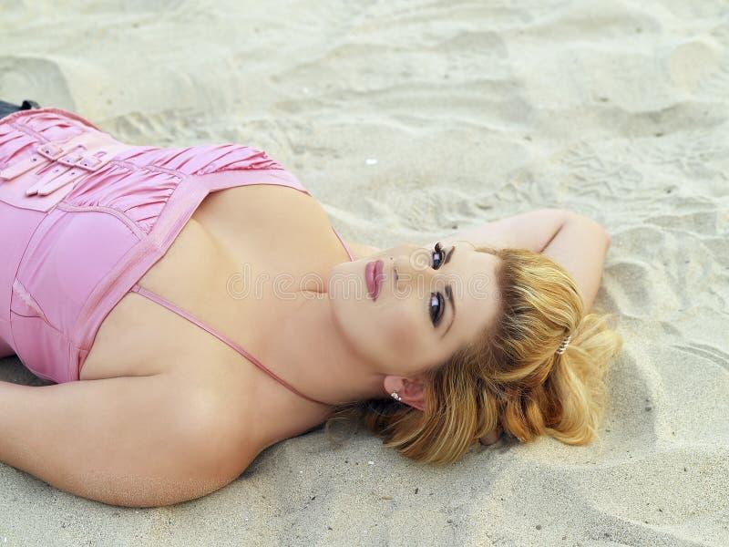Mujer caucásica rubia regordeta joven en la playa imagen de archivo