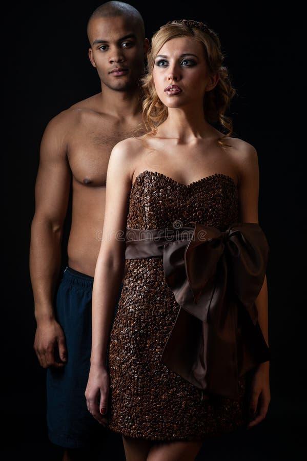Mujer caucásica sensual joven en el vestido hecho de la situación de los granos de café y del hombre negro sobre fondo anaranjado foto de archivo libre de regalías