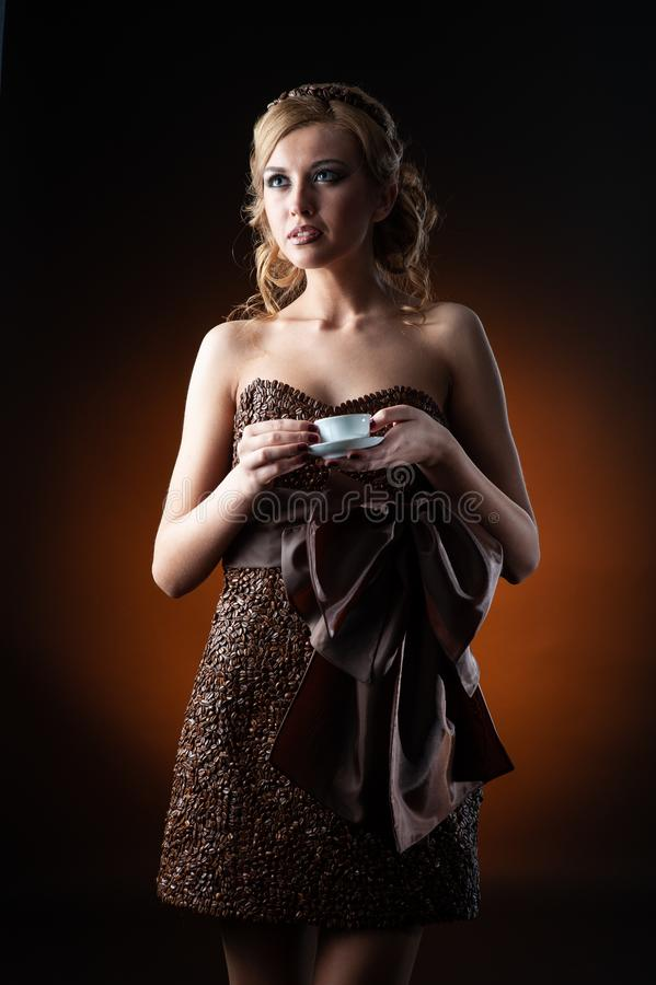Mujer caucásica sensual joven en el vestido hecho de la situación de los granos de café y del hombre negro sobre fondo anaranjado foto de archivo