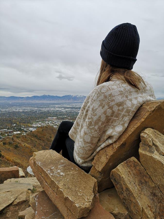 Mujer caucásica sentada en un sofá rocoso disfrutando de las vistas desde la caminata en Living Room Trailhead fotos de archivo libres de regalías