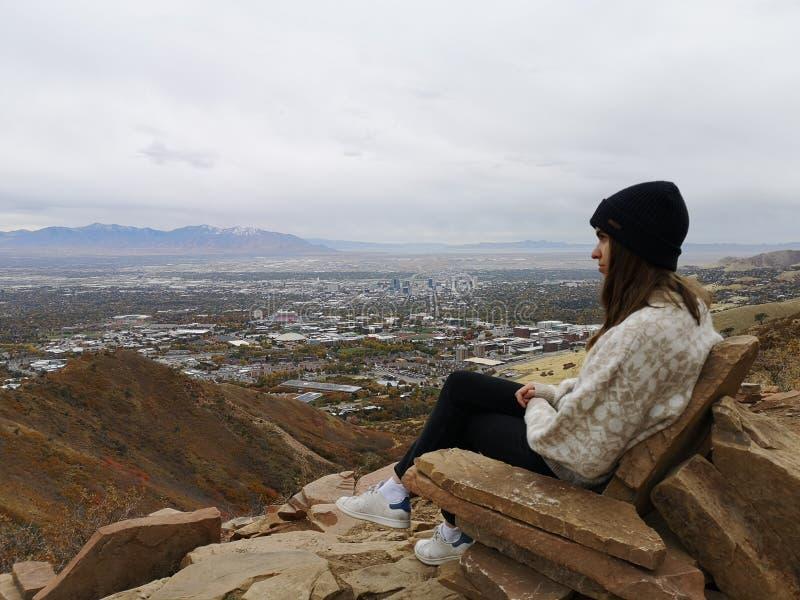 Mujer caucásica sentada en una silla rocosa disfrutando de las vistas desde la caminata en Living Room Trailhead imagenes de archivo