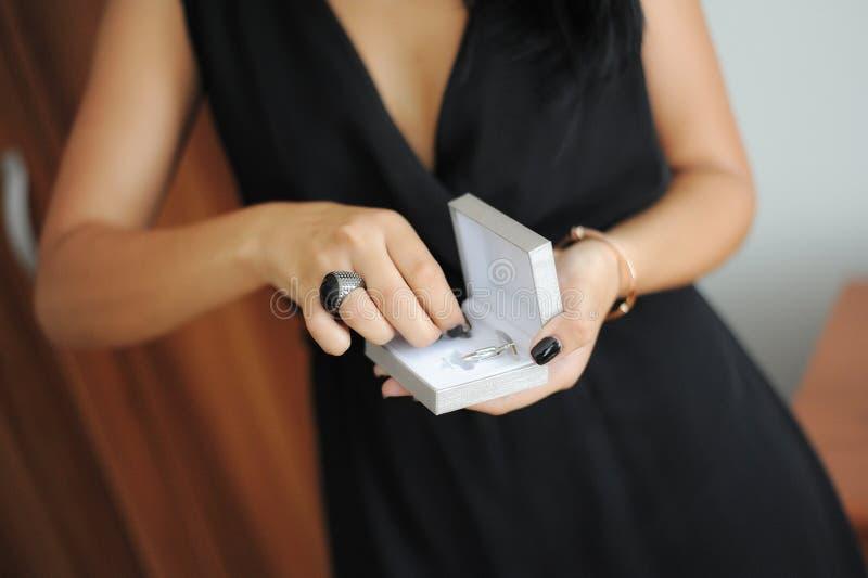 Mujer caucásica vestida en un vestido negro elegante que sostiene un pequeño joyero con un par de vínculos de puño de plata imagenes de archivo