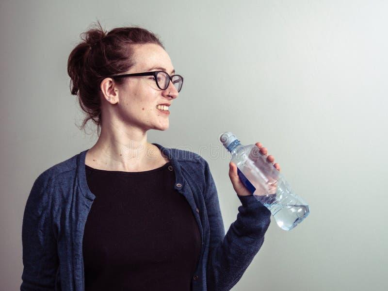 Mujer cauc?sica que sonr?e con una botella de agua fotos de archivo libres de regalías