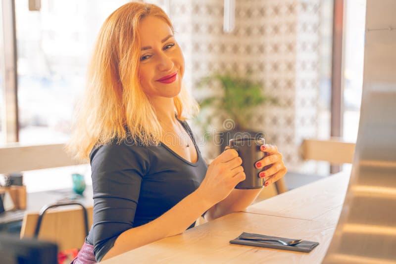Mujer cauc?sica redheaded feliz bonita en la taza negra de las bebidas de la camisa de caf? en el caf? moderno solamente fotografía de archivo libre de regalías