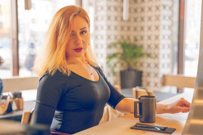 Mujer cauc?sica redheaded feliz bonita en la taza negra de las bebidas de la camisa de caf? en el caf? moderno solamente imágenes de archivo libres de regalías