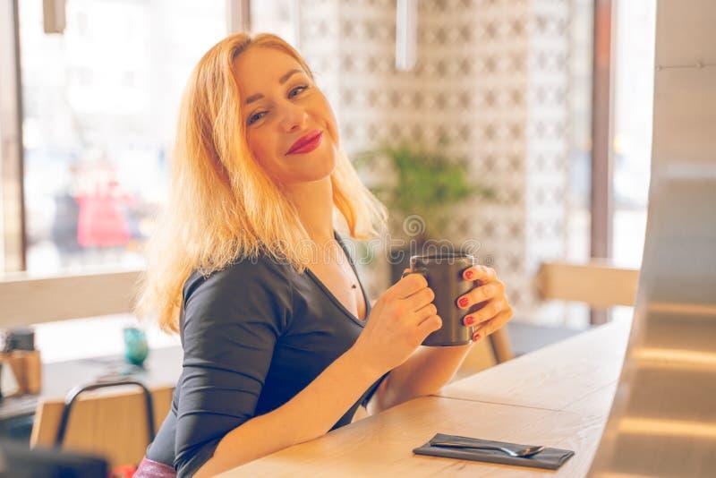 Mujer cauc?sica redheaded feliz bonita en la taza negra de las bebidas de la camisa de caf? en el caf? moderno solamente foto de archivo